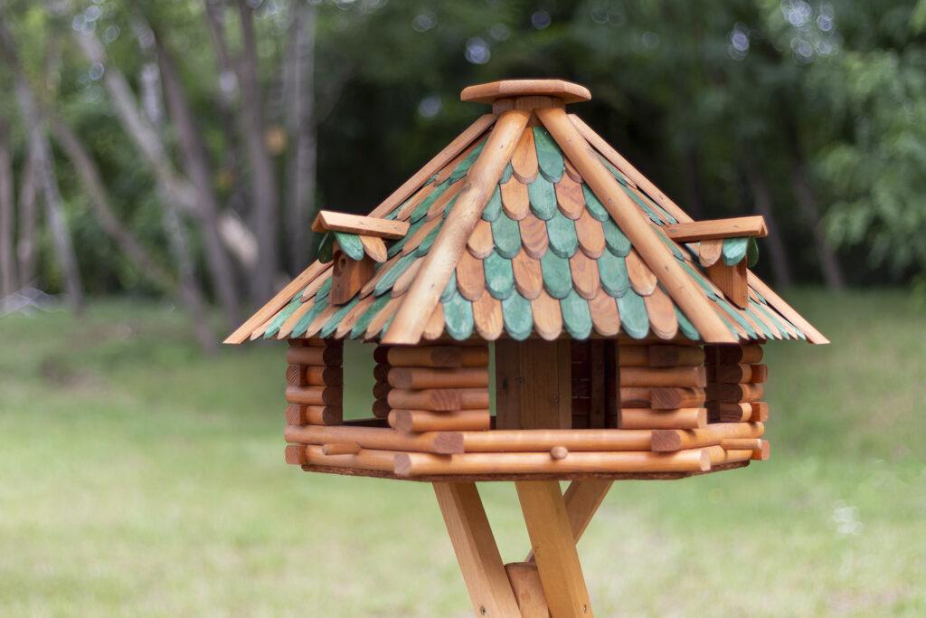Vogelhaus mit verziertem Dach aus Holzschindeln und großen Einflugöffnungen an mehreren Seiten.