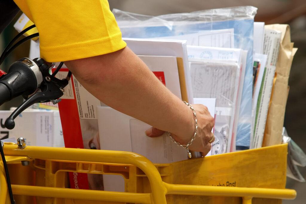 Postzustellerin greift einen Stapel Briefe und Zeitschriften.